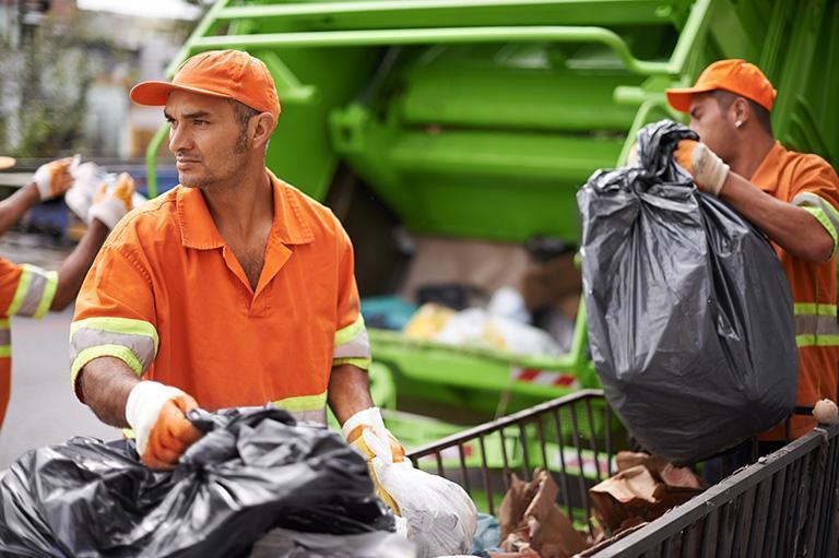 mężczyzna zbierający kubły ze śmieciami