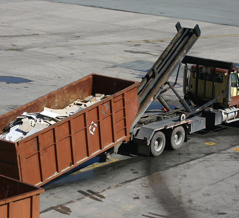 ciężarówka podnosząca kontener ze śmieciami